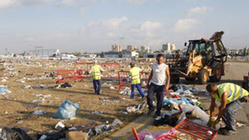 Personal de los servicios de limpieza recoge los restos y desperdicios que han quedado en el suelo de la Base Aérea de Cuatro Vientos de Madrid. Foto. EFE