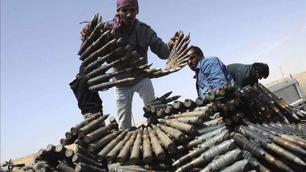 Miembros de las fuerzas rebeldes en Libia preparaban ayer munición antiaérea en una de sus posiciones en un puesto de control entre Ajdabiya y Brega, Libia. EFE