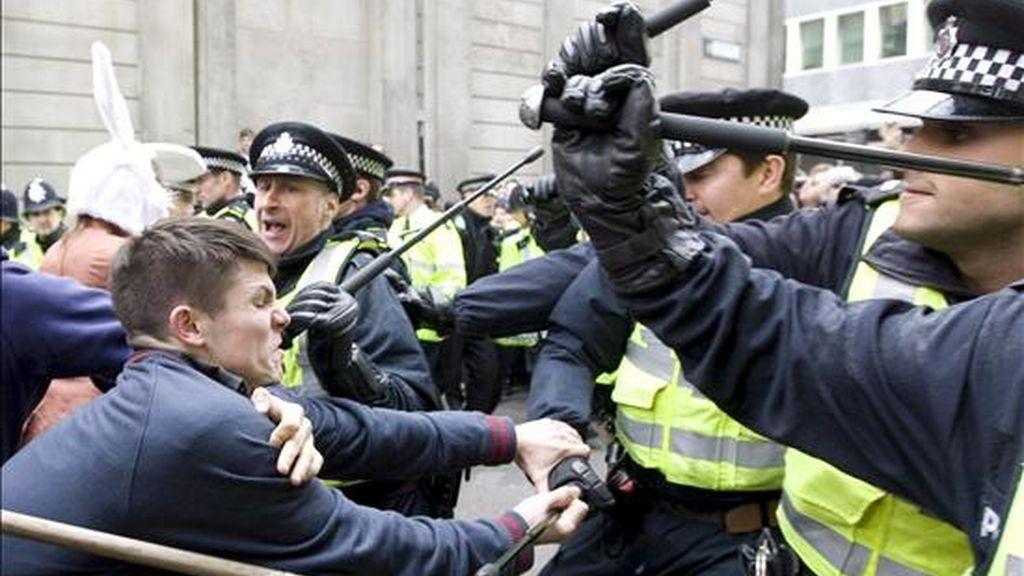 Agentes de policía se enfrentan a un grupo de manifestantes que protestaban en el exterior de una sucursal del Banco de Inglaterra, hoy miércoles 1 de abril de 2009 en Londres, Reino Unido.En medio de unas medidas de seguridad sin precedentes, miles de personas han empezado a llegar hasta el centro financiero de Londres para expresar su rechazo a los excesos del sistema capitalista, un día antes de la cumbre del G20. EFE