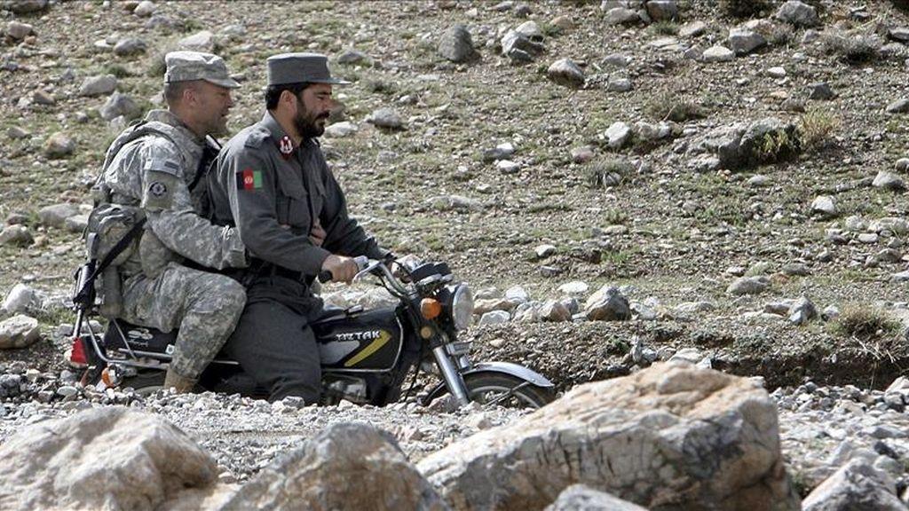 Un soldado estadounidense (izda) viaja en moto con un policía afgano (dcha) en el distrito de Jaghory en la provincia de Ghazni (Afganistán) este sábado. EFE