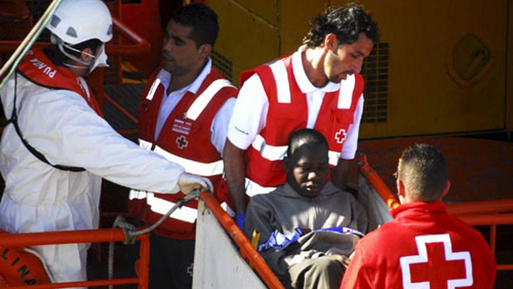 Voluntarios de Cruz Roja trasladan a uno de los 65 inmigrantes interceptados. Foto: EFE.