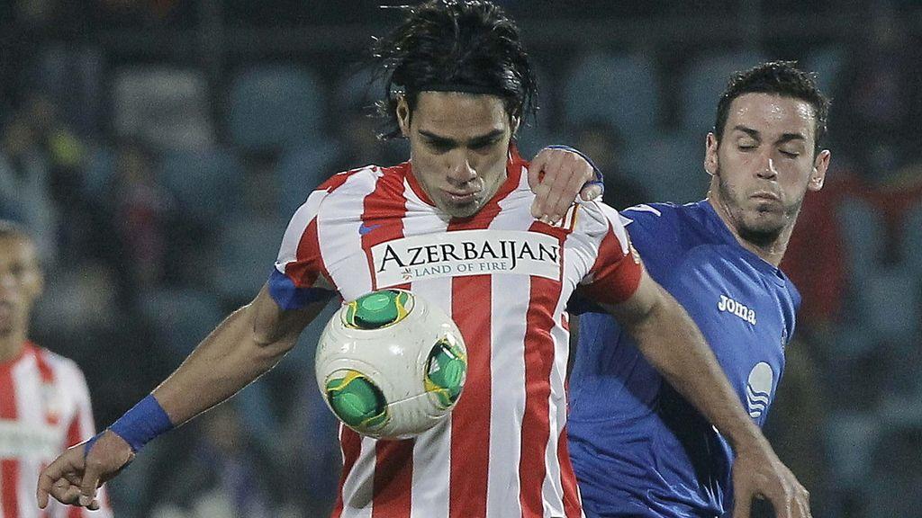 El delantero colombiano del Atlético de Madrid Radamel Falcao (i), controla el balón ante el delantero del Getafe Álvaro Vázquez