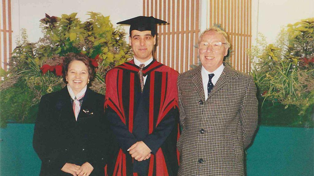 Joan y Walter Moss posan en la graduación de su hijo