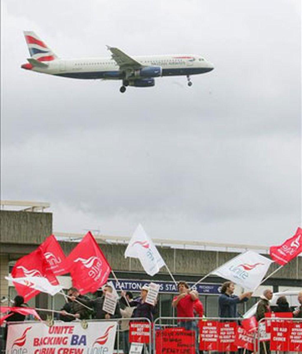 Un avión de la aerolínea British Airways se acerca a una pista de aterrizaje mientras trabajadores de la empresa protestan. Foto: EFE.