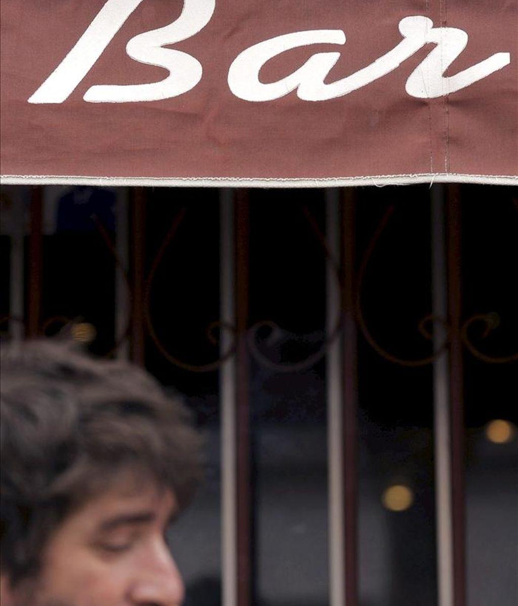 Un hombre fuma en la puerta de un bar de Valladolid, en el primer día de entrada en vigor de la nueva Ley Antitabaco en España. EFE/Archivo