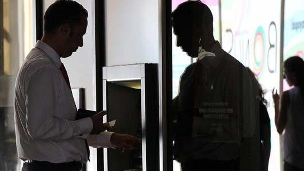 Un cliente retira dinero de un cajero automático