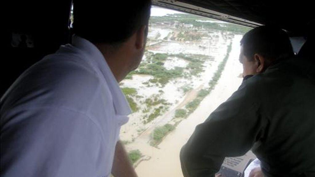 El presidente de Venezuela, Hugo Chávez (d), sobrevueló este viernes una zona afectada por las lluvias en Tucacas (Venezuela). Los aguaceros han dejado al menos 34 muertos y más de 70.000 afectados en todo el país. EFE