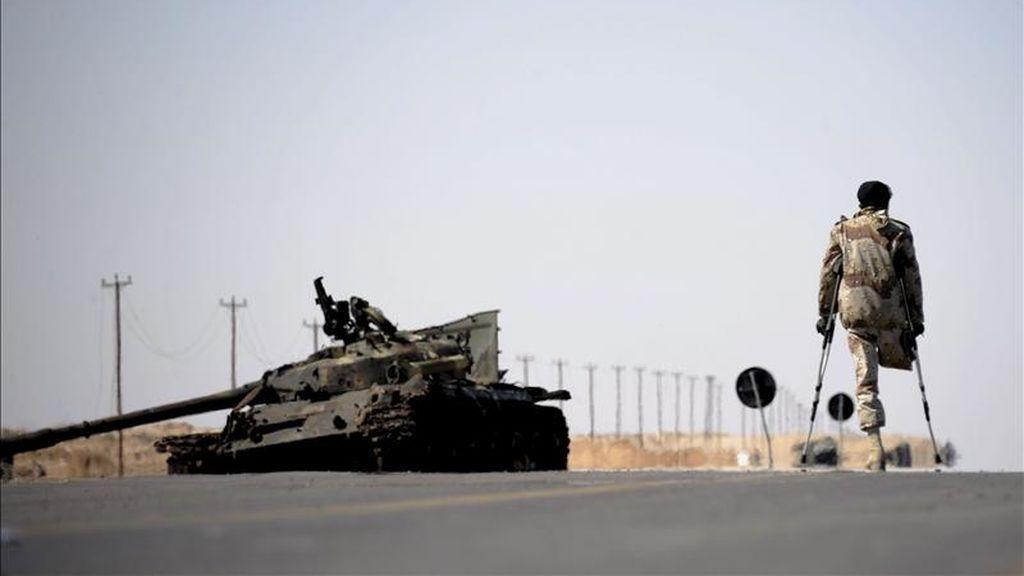 Un combatiente rebeldes libio pasa junto a los restos de un tanque en un puesto de control montado entre las localidades libias de Ajdabiya y Brega el pasado12 de abril. EFE/Archivo