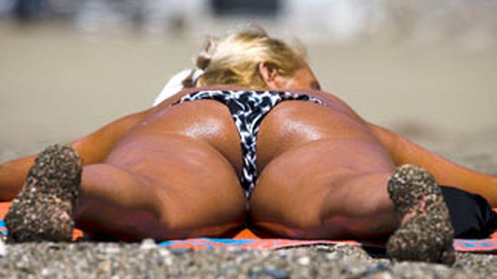 Una mujer toma el sol en La Malagueta. Foto: EFE.
