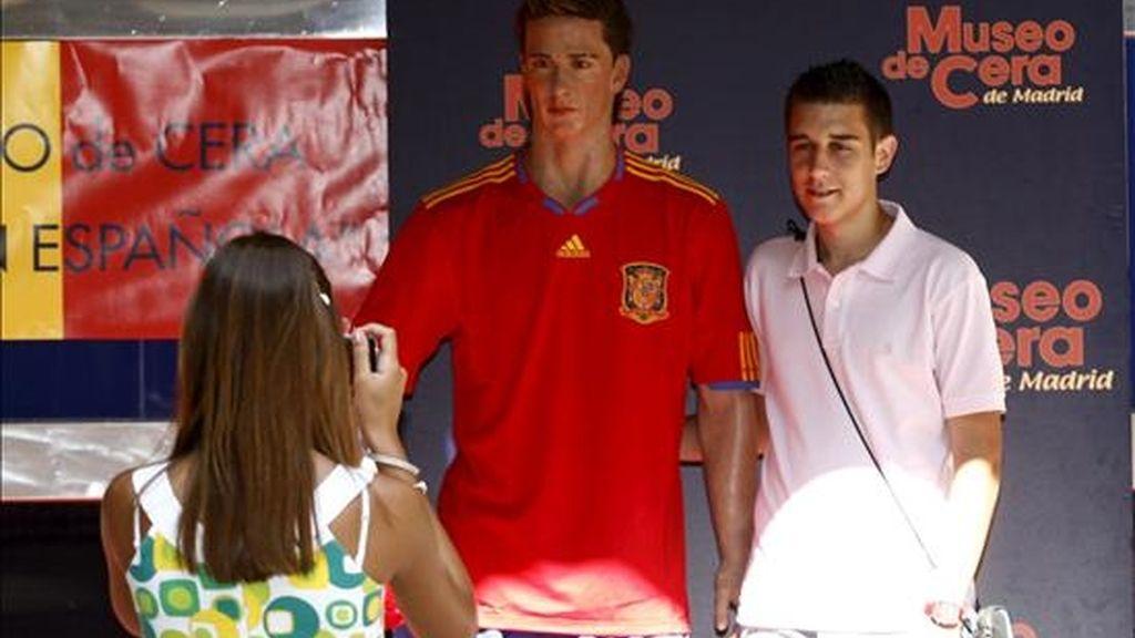 Un chico se fotografía junto a la figura de Torres que el Museo de Cera de Madrid ha sacado a la calle vestida con la camiseta roja de la Selección Española, en un gesto de apoyo al equipo para que gane mañana la final del campeonato mundial de Sudáfrica 2010. EFE