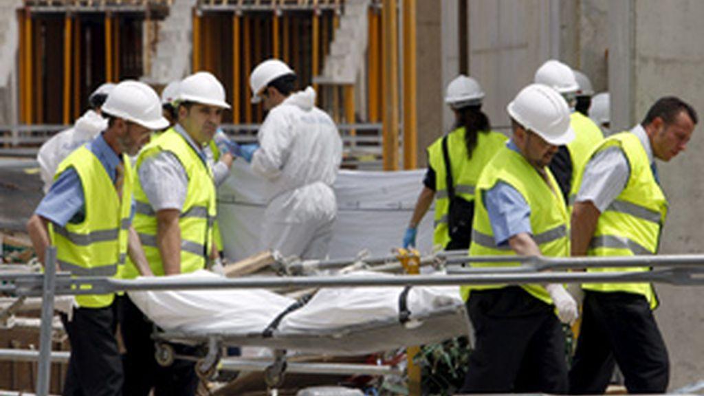 Miembros de la funeraria retiran uno de los cadáveres. Foto: EFE.