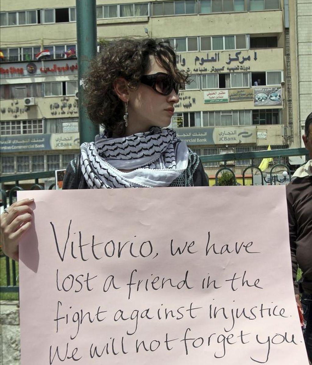 Una activista muestra una pancarta mientras participa en una protesta de repulsa al asesinato del joven activista italiano Vittorio Arrigoni, quien apareció muerto la madrugada del 14 de abril en Gaza tras ser secuestrado por un grupo extremista salafista, hoy sábado 16 de abril de 2011 en Naplusa, Cisjordania. EFE
