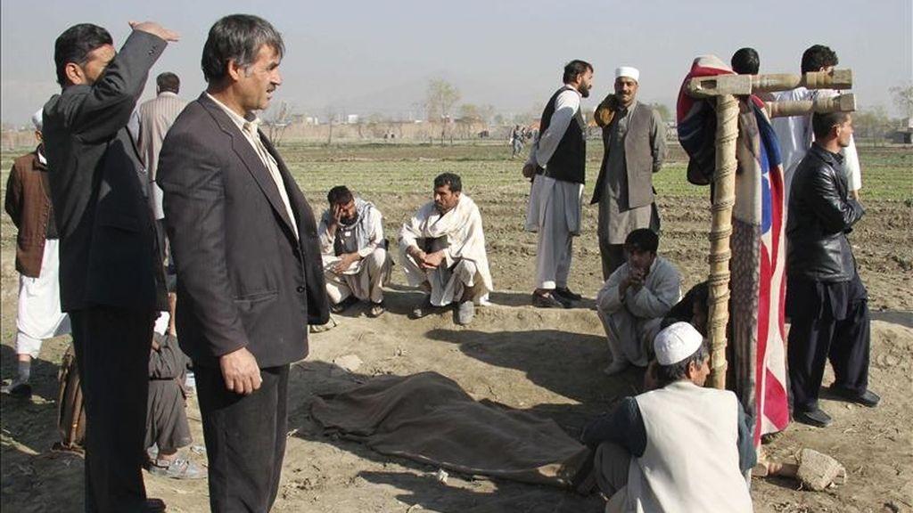 Varios afganos observan el cadáver tapado de una de las víctimas que falleció cuando un grupo de insurgentes atacaron hoy una base militar estadounidense en Kabul (Afganistán). EFE