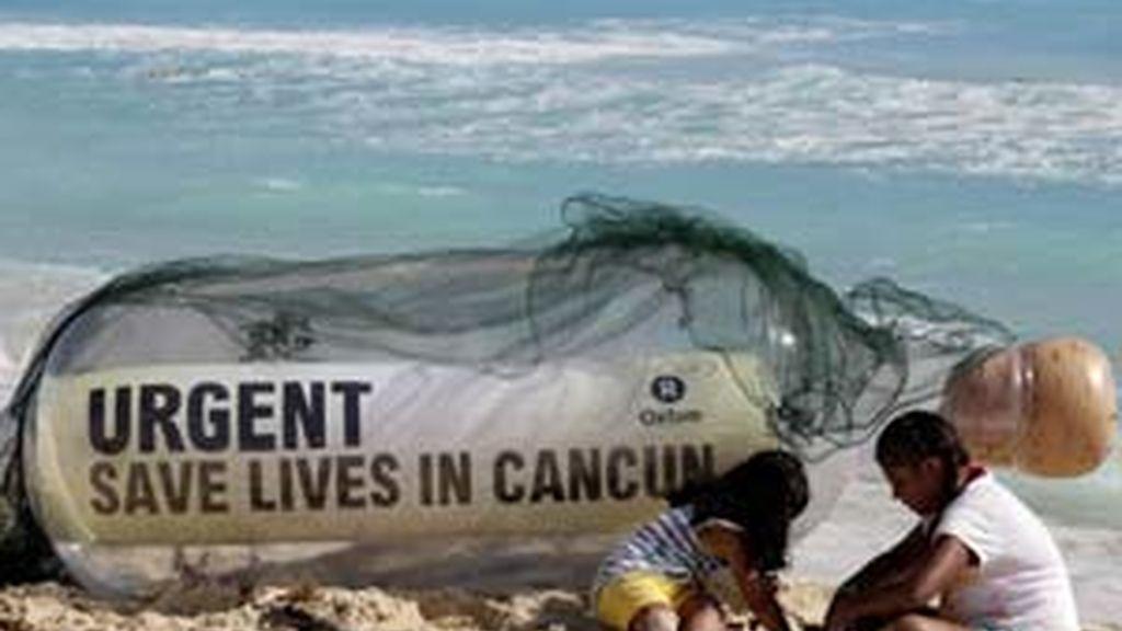 Una botella gigante contiene un mensaje de Oxfam en una playa de Cancún. Foto: Gtres