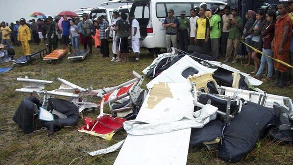 Una multitud observa los restos del avión estrellado hoy cerca del aeropuerto de Caimana (Indonesia). EFE
