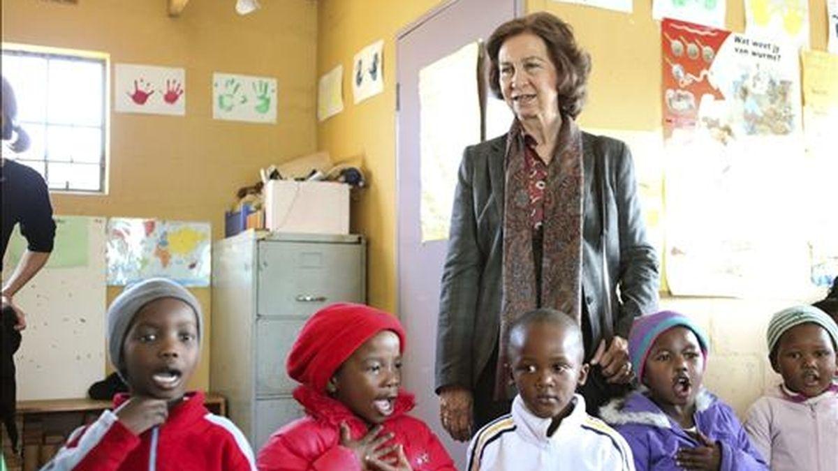 La reina Sofía junto a varios niños durante la visita que ha realizado a un centro que utiliza el fútbol como medio educativo en el barrio de Khayelitsa, en Ciudad del Cabo. EFE
