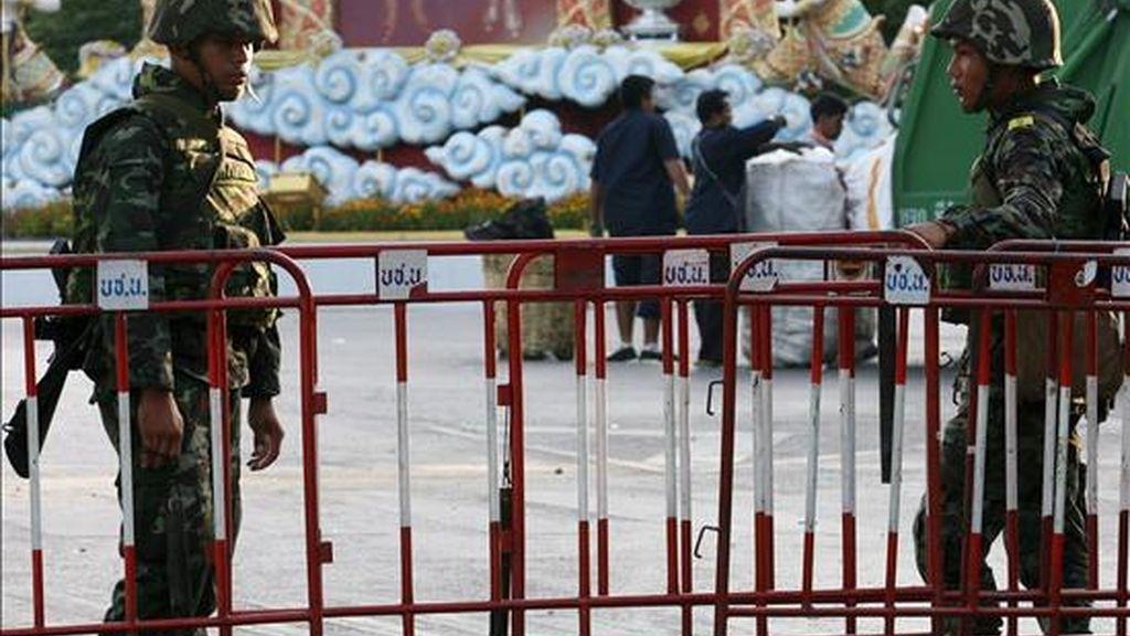 """Soldados tailandeses vigilan mientras trabajadores limpian el área cerca a la Casa de Gobierno en Bangkok (Tailandia) hoy, 15 de abril de 2009. Un tribunal de justicia de Tailandia emitió órdenes de arresto contra el ex primer ministro Thaksin Shinawatra y 13 aliados por las violentas protestas organizadas por sus seguidores, los """"camisetas rojas"""", para derribar el Gobierno y que han causado dos muertos y 123 heridos. EFE"""