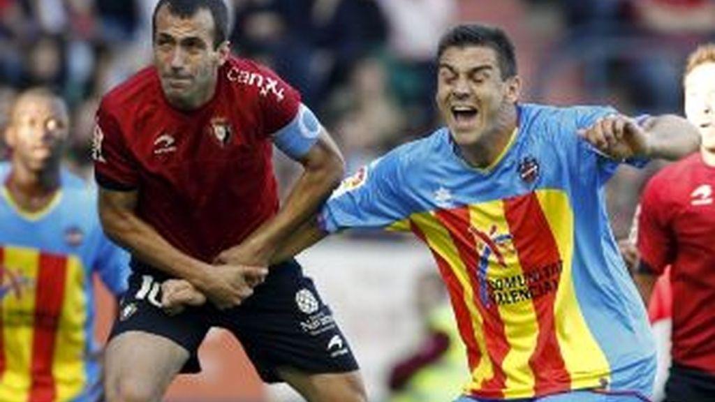 El centrocampista del CA Osasuna, Francisco Puñal (i), lucha la pelota aérea con el defensa del Levante UD, Sergio Ballesteros. EFE