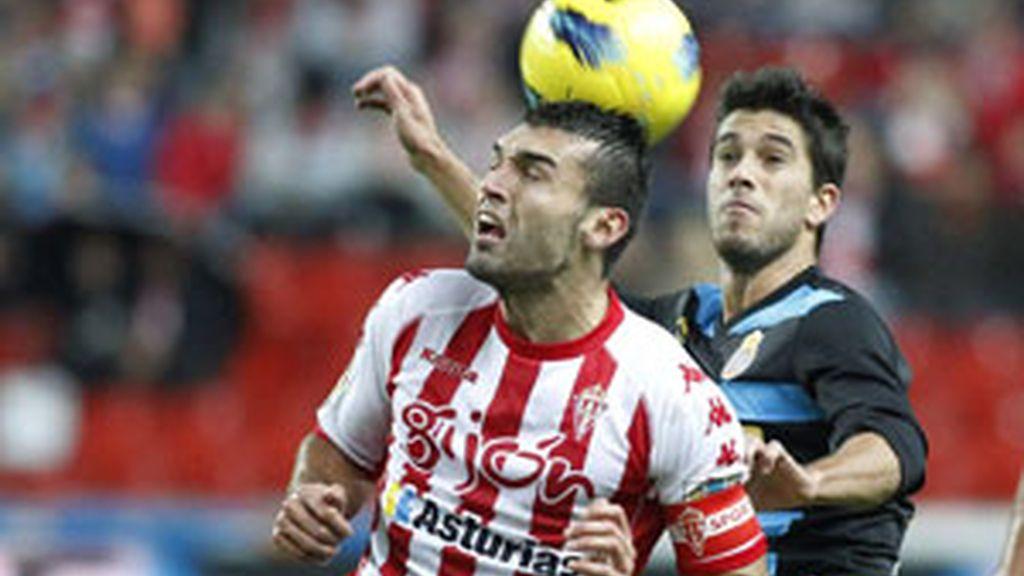 El delantero del Sporting de David Barral cabecea un balón ante el defensa del Espanyol Dídac Vila FOTO: EFE