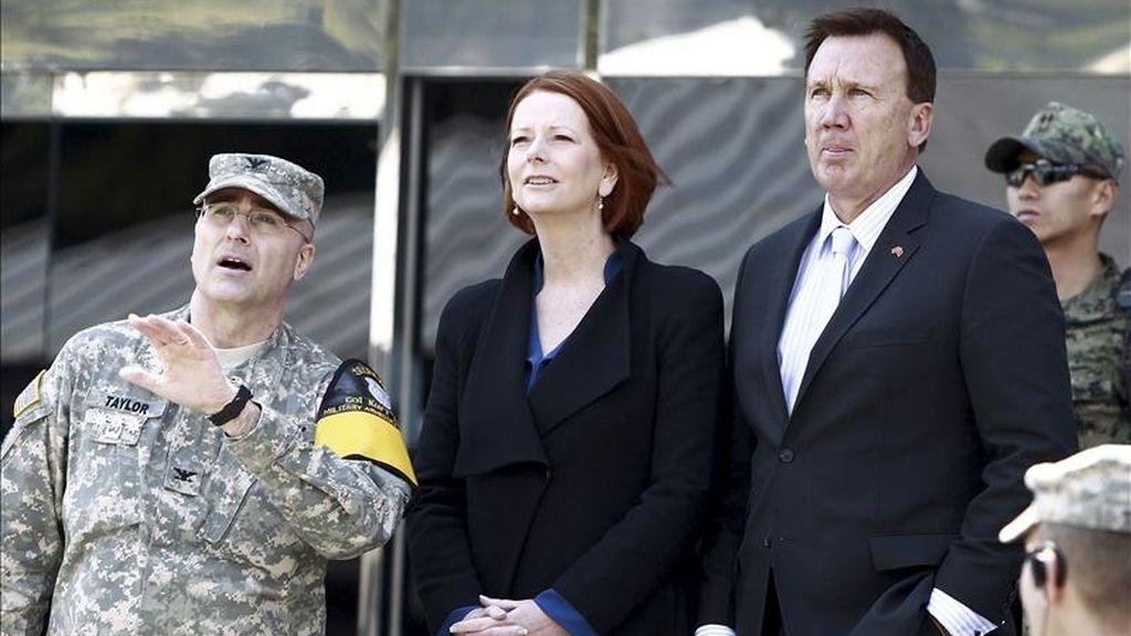 La primera ministra australiana, Julia Gillard (c), y su pareja Tim Mathieson (dcha), escuchan a un responsable de la Comisión Supervisora de Naciones Neutrales (izq) durante la visita de la mandataria austrailana a la línea de demarcación militar de la zona desmilitarizada situada en la localidad fronteriza de Panmunjom (Corea del Sur). EFE