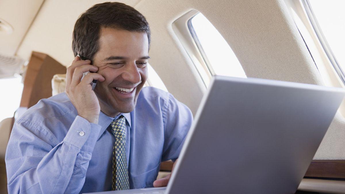 Un ejecutivo habla por teléfono durante el vuelo de un avión