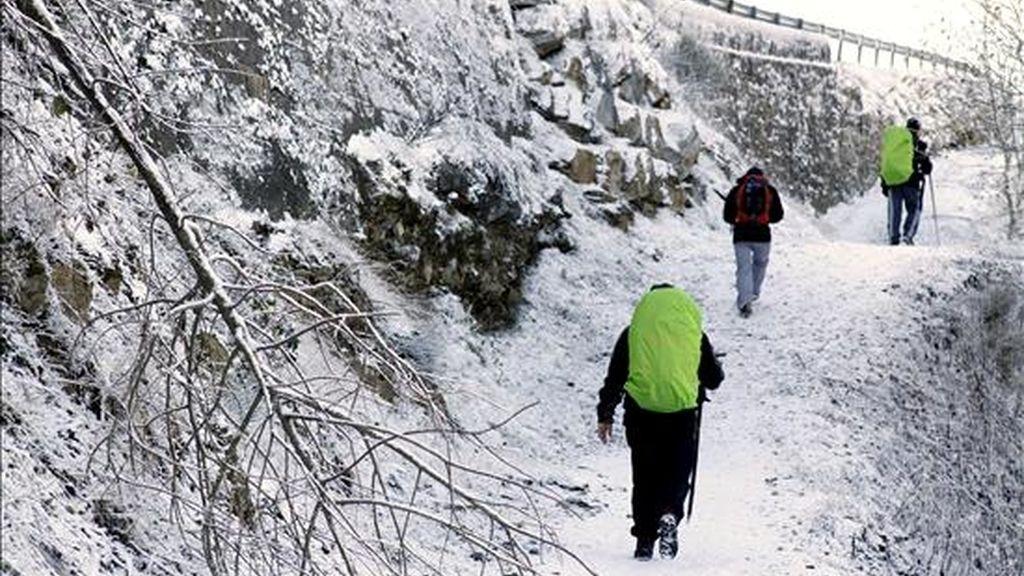 Varios peregrinos de Mallorca caminan por un paisaje completamente blanco, en el pueblo de Liñares, en O Cebreiro, debido a las intensas nevadas que se registran en la montaña de Lugo. EFE