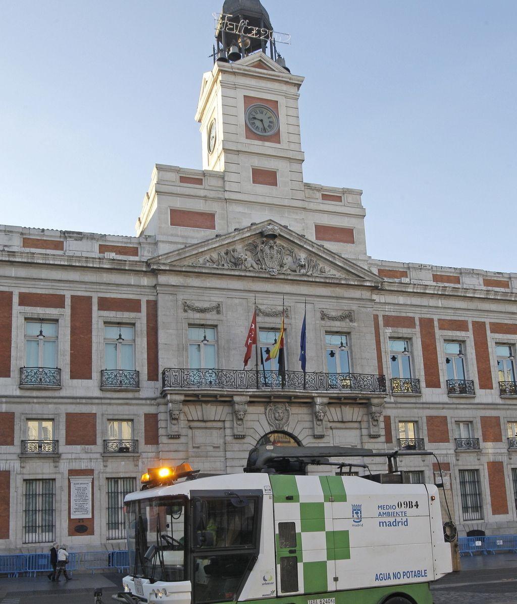 Un vehículo de los servicios de limpieza municipales retira de la Puerta del Sol los últimos restos de las celebraciones de la Nochevieja, en la primera mañana del nuevo año 2012