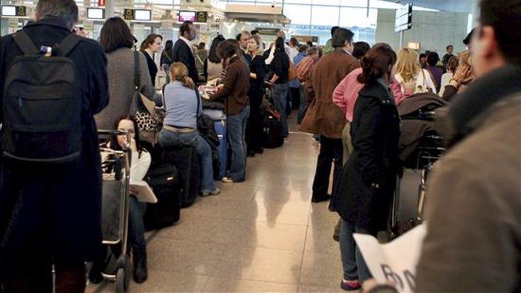 Varios pasajeros hacen cola frente a los mostradores de facturación en el aeropuerto del Prat de Llobregat (Barcelona) para volar, después de que el espacio aéreo español se cerrase ayer cuando los controladores abandonaron masivamente sus puestos de trabajo, y haya sido reabierto durante la tarde de hoy. EFE