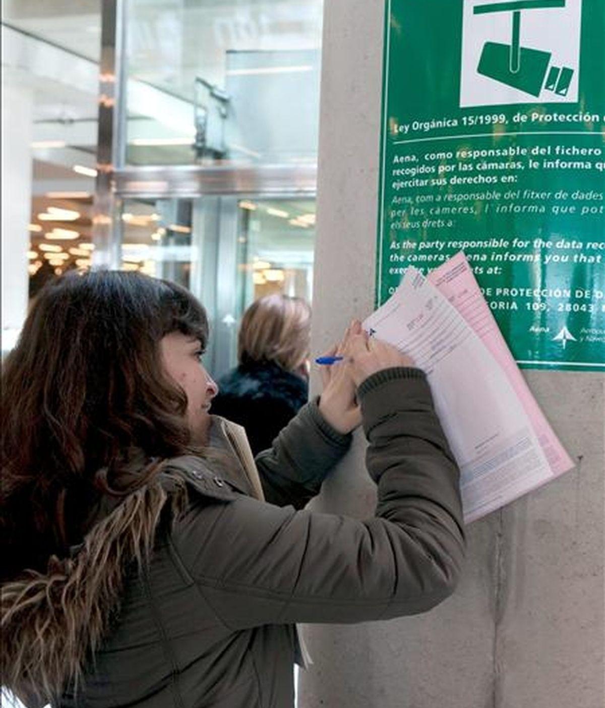 Una mujer rellena una hoja de reclamaciones en el aeropuerto de Son San Joan, en Palma de Mallorca, cuyo cierre provocado por el abandono masivo del puesto de trabajo de los controladores aéreos ha afectado ya a miles de viajeros. EFE