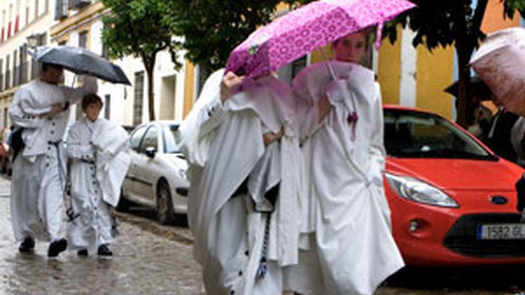 Miembros de la Cofradía de Monte-Sión de Sevilla regresan a su casa bajo la lluvia, en la capital andaluza. Foto: EFE