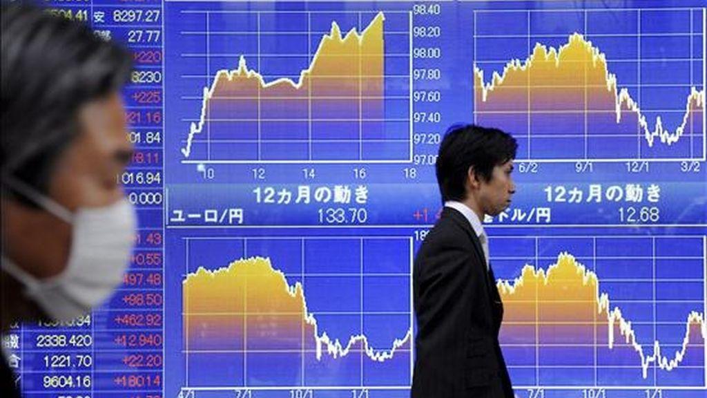 Dos personas pasan por delante de un panel electrónico en el que se muestran los valores de la Bolsa, en Tokio (Japón). EFE/Archivo