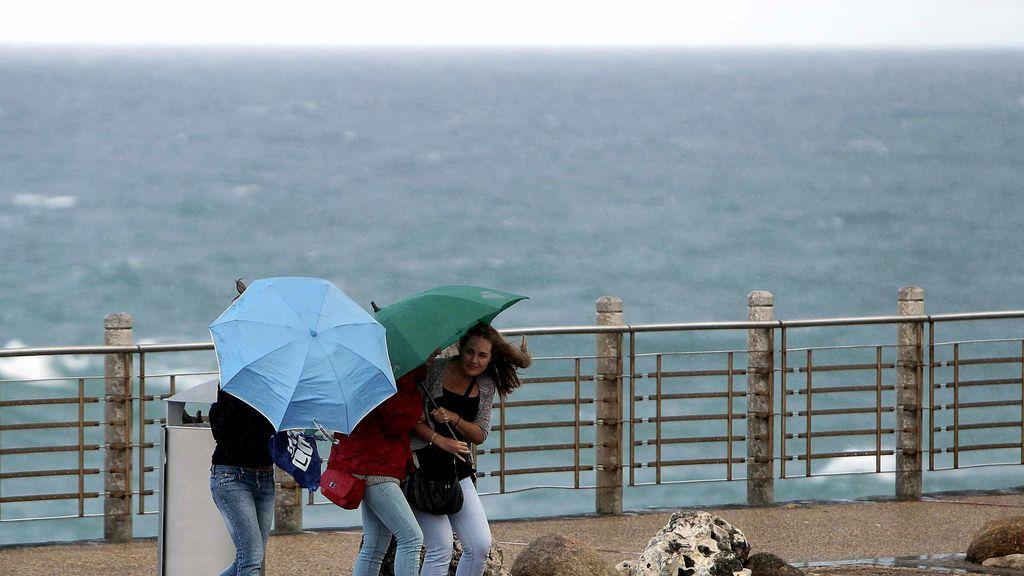 Tres turistas se protegen del fuerte viento y las precipitaciones en San Sebastián