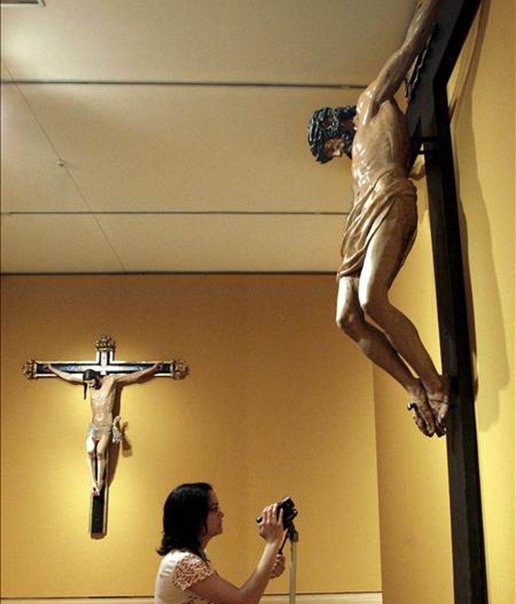 """Una joven graba el """"Cristo Crucificado"""", de Juan de Anchieta, con el """"Cristo Crucificado"""", del escultor Damián Forment al fondo, obras que se exponen desde hoy en el Museo de Bellas Artes de Bilbao dentro de la muestra que recoge los fondos más significativos de la época renacentista del Museo de Zaragoza. EFE"""