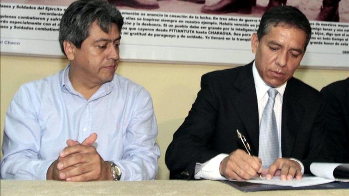 El gobernador del departamento de Central de Paraguay, Carlos Amarilla (d), firma un documento  en la localidad de Fernando de la Mora (Paraguay), durante un acto, ante el destituido gobernador boliviano Mario Cossío (i). EFE