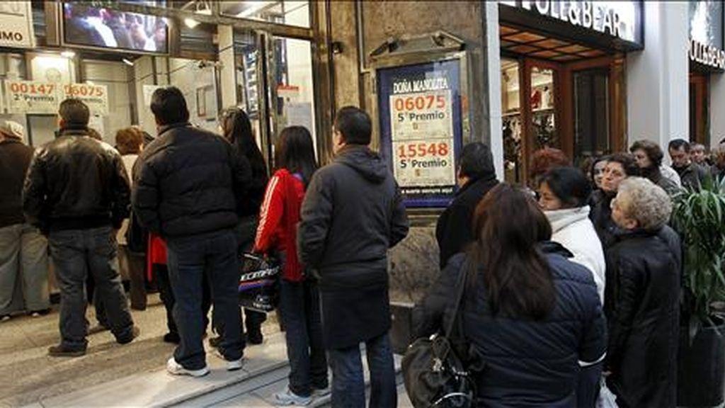 """Varias personas guardan cola en una céntrica administración madrileña para comprar sus décimos antes de la celebración del sorteo extraordinario de """"El Niño"""". EFE"""