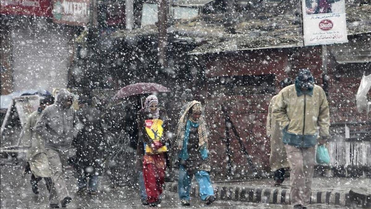 Varias personas caminan bajo la nieve durante una tormenta en Srinagar, capital de verano de la Cachemira india hoy, viernes, 14 de enero de 2011. EFE