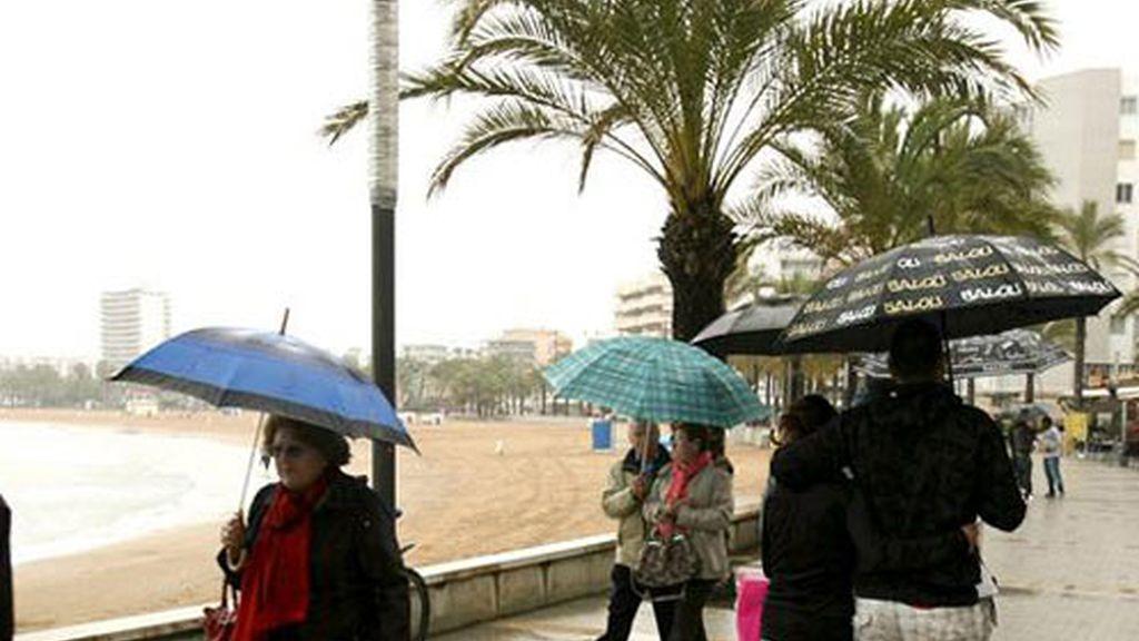 Varios turistas caminan por el paseo marítimo de la playa de levante de la localidad tarraconense de Salou.