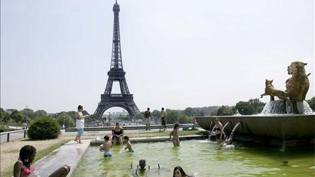 Un grupo de jóvenes se refresca en la fuente del Trocadero, frente a la Torre Eiffel, en París (Francia). EFE/Archivo