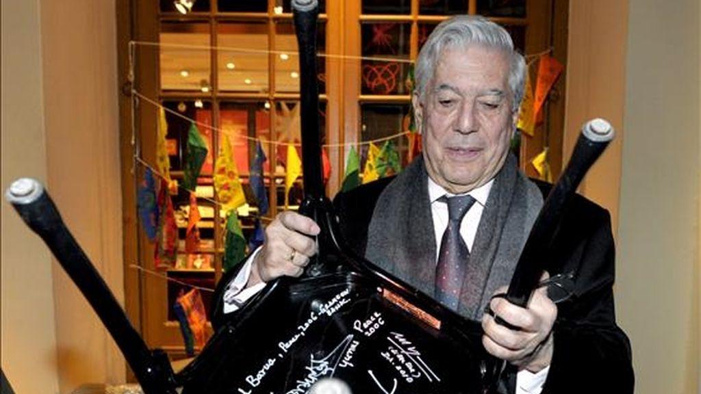 El escritor hispano peruano Mario Vargas Llos levanta una silla en cuyo reverso aparecen las firmas de varios premios Nobel durante su visita al Museo Nobel en Estocolmo, Suecia. EFE