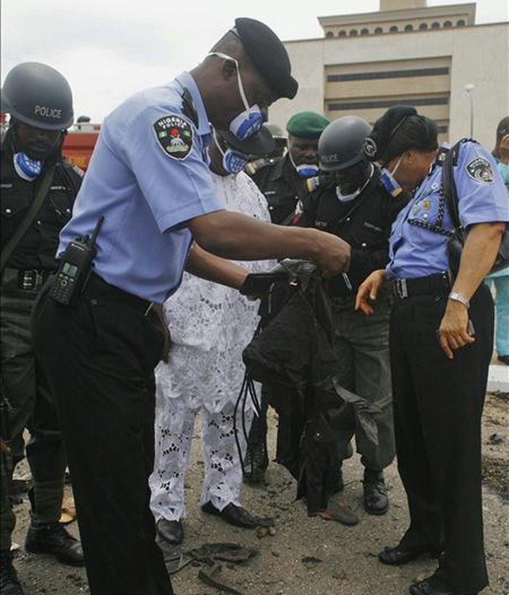 Oficiales de la policía nigeriana observan el uniforme de un compañero asesinado a consecuencia del atentado del Movimiento para la Emancipación del Delta del Níger (MEND), el principal grupo guerrillero de Nigeria, durante los actos oficiales del cincuentenario de la independencia del país. EFE