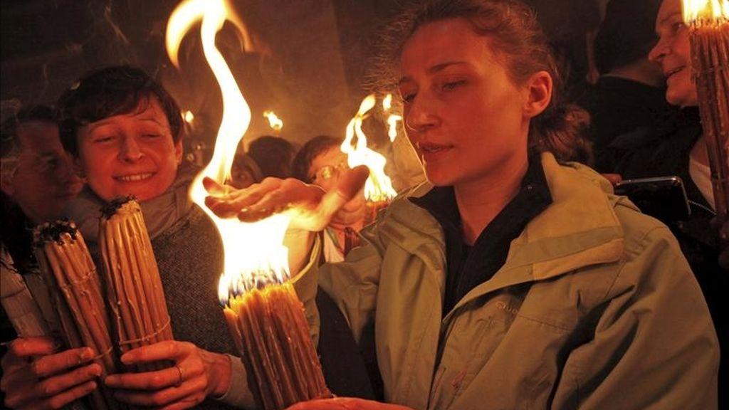 Una cristiana ortodoxa coloca su mano sobre las llamas de su vela tras haber recibido el Fuego Sagrado hoy en el templo del Santo Sepulcro, en Jerusalén. EFE