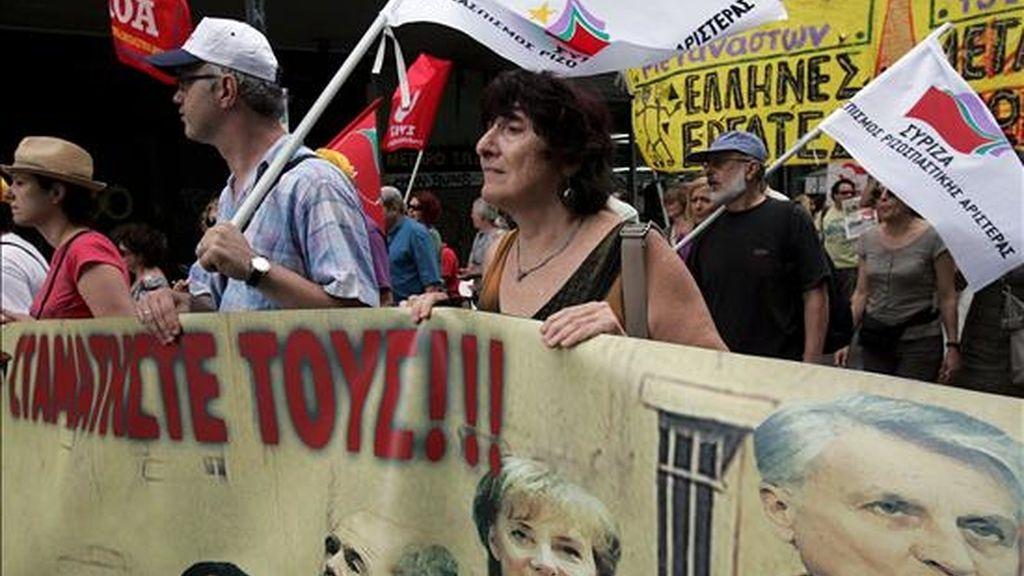 """Manifestantes portan una pancarta con los retratos del presidente del Banco Central Europeo, (BCE) Jean Claude Trichet, la canciller alemana, Angela Merkel, el primer ministro griego, Yorgos Papandréu, y el ministro de Finanzas griego, Yorgos Papaconstantínu, y la frase: """"¡Paradles!""""en Atenas (Grecia), el 8 de julio. EFE"""