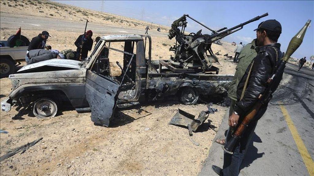 Dos rebelde libios se detiene ante una camioneta calcinada a un lado de la carretera entre Bengasi y Briga (Libia), hoy, martes 5 de abril de 2011. EFE