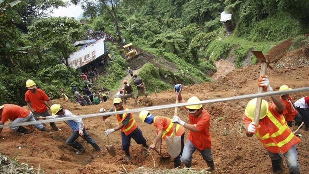 Voluntarios y miembros de los equipos de rescate reanudan la búsqueda de más de una veintena de personas, sepultadas 24 horas antes a causa de un alud de tierra, hoy en la localidad de Kingking, en la provincia de Valle Compostela, a 980 kilómetros al sur de Manila (Filipinas). EFE