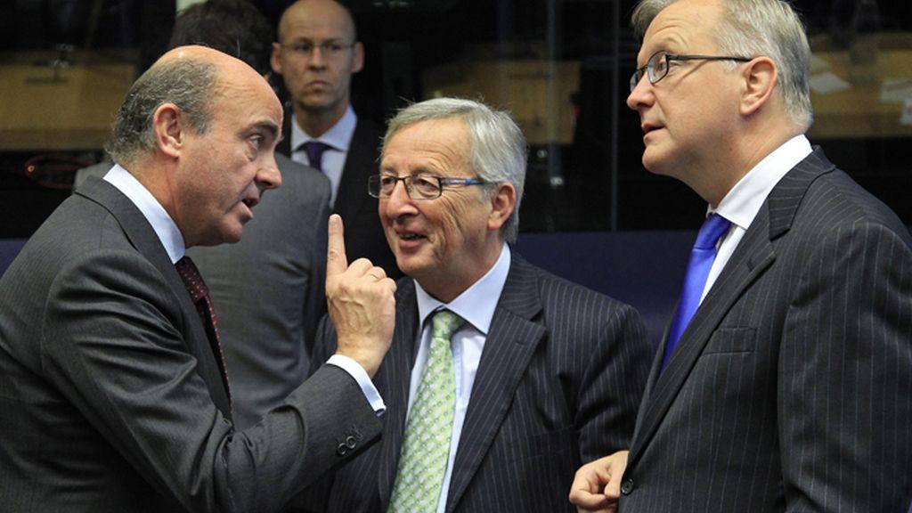 Luis de Guindos, conversa con Jean-Claude Juncker y Olli Rehn durante la reunión del Eurogrupo en Luxemburgo