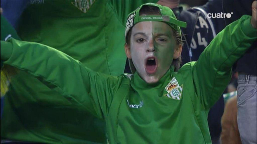 Un niño con la cara pintada de verdiblanca en la grada