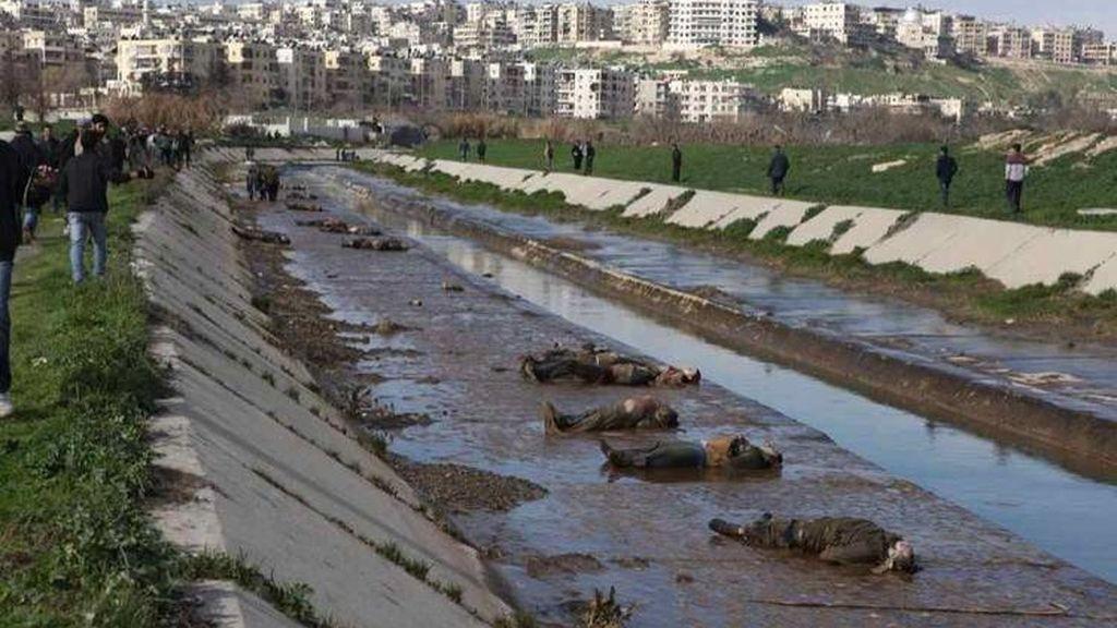 Sirios observan los cadáveres que aparecieron en un pequeño canal situado en un barrio de Alepo bajo control del Gobierno