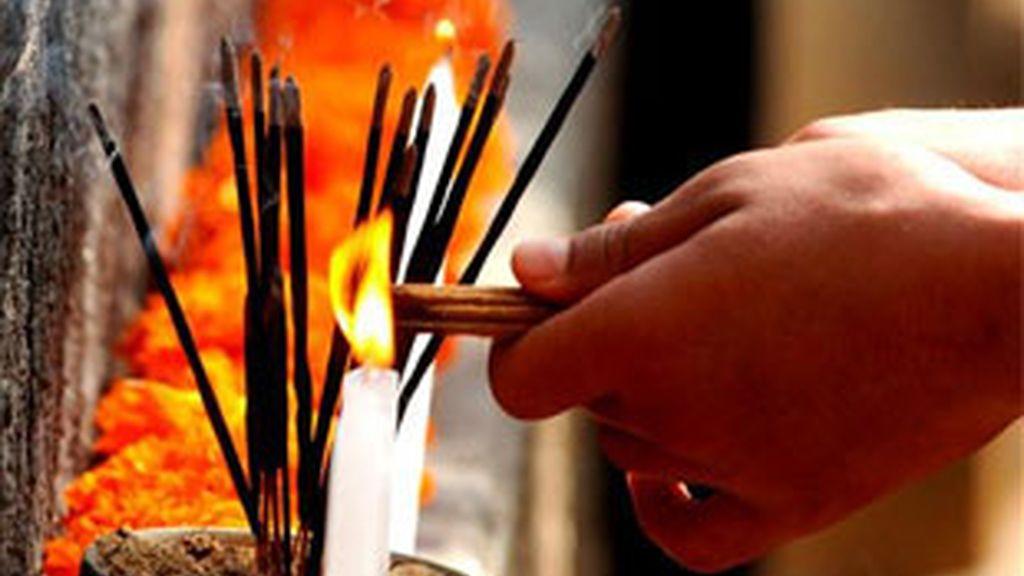 Un monje budista quema incienso.
