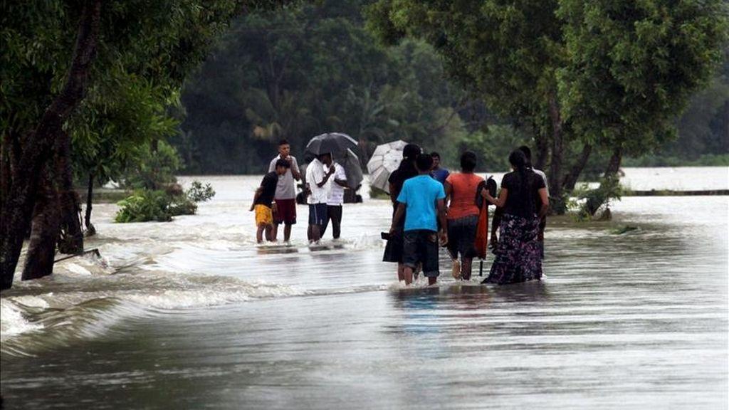 Habitantes de Gampaha vadean un campo inundado a 40 kilómetros de Colombo en Sri Lanka, durante unas inundaciones registradas en mayo de  2010. EFE/Archivo