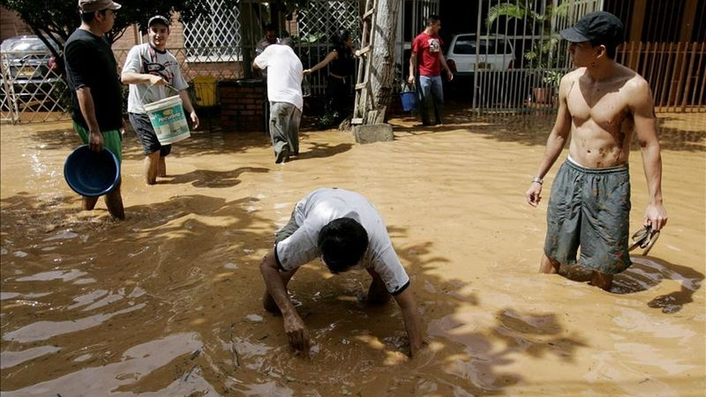 Varias personas intentan despejar las calles inundadas en una zona de Cali (Colombia), tras el desbordamiento de un sistema de desagüe de aguas residuales debido a las fuertes lluvias de la ola invernal en el país. EFE